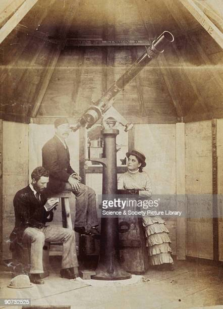 Photograph showing two men and a woman with a telescope in a wooden observatory building. The equipment and structure are part one of five separate...