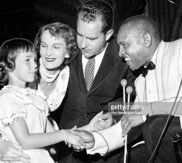 A photograph showing Vice President Richard Nixon his wife Pat and their daughter Julie who is greeted with a handshake by bandleader Lionel Hampton...