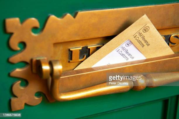 Photograph shows a front door letter box with HMRC envelope, Her Majestys Revenue and Customs reminding of the date that self-assessment tax returns...