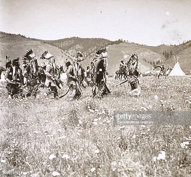 Photograph shows a group of men dancing during a traditional Sioux pow-wow, South Dakota, early 20th century. They wear ceremonial headdresses in a...