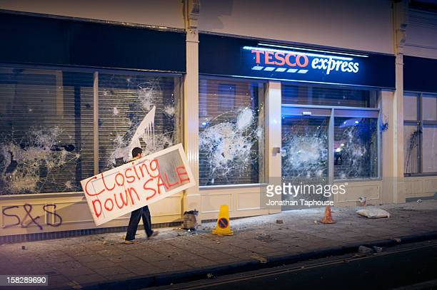 Photograph shows a protester carrying a closing down sale sign to the recently vandalised TESCO store in Stokes Croft BRISTOL Around 8pm on the 21st...