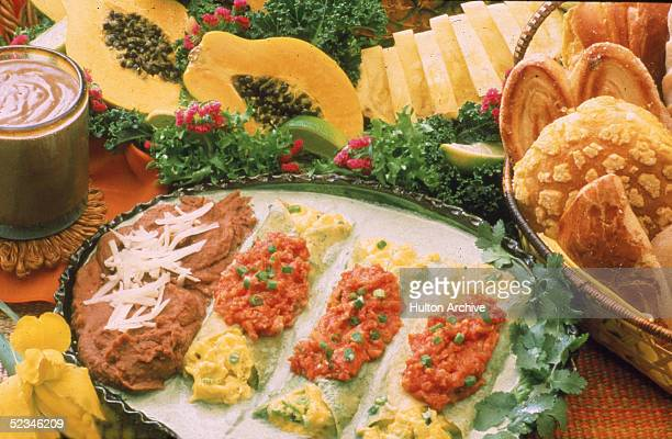 Photograph shows display of Mexicanthemed food items including eggs wrapped in tortillas and smothered in salsa refried beans breads and pastries...