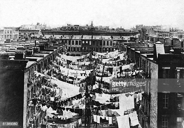 Photograph shows laundry drying on clotheslines in the backyards of New York City tenement slums circa 1900