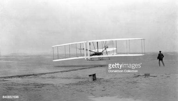 Photograph shows the first powered controlled sustained flight Orville Wright at the controls of the machine lying prone on the lower wing with hips...