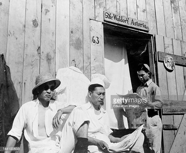Photograph Shows Three Interned Japanese Men Sitting By A Wooden Building With The Words The Waldorf Astoria Written Over The Doorway Puyallup...