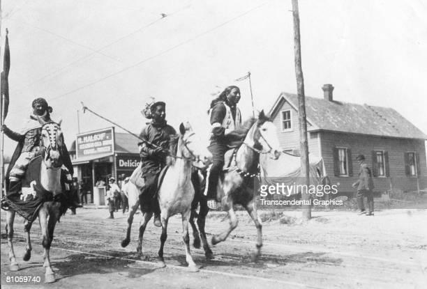 A photograph shows three Native American men riding horses during Buffalo Bill's Wild West Show United States late 19th century They race down a road...