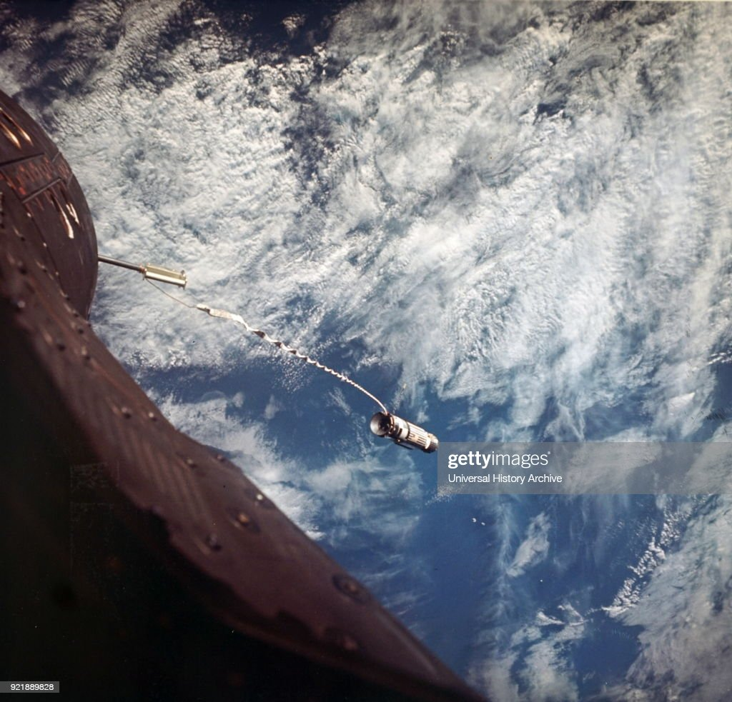 Photograph taken aboard the Gemini XII - view of the Agena Target Docking Vehicle at the end of the tether securing it to NASA's Gemini XII spacecraft. Dated 20th century.