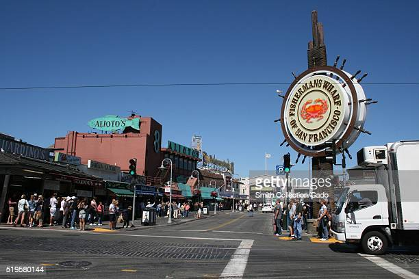 A photograph taken at an intersection in Fisherman's Wharf people are lined up waiting to cross the street while a commercial truck waits at a...