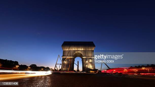 Photograph taken at dusk on September 16, 2021 shows the Arc de Triomphe in Paris, wrapped in silver-blue fabric, as it was designed by late artist...