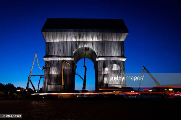 Photograph taken at night on September 16, 2021 shows the Arc de Triomphe in Paris, wrapped in silver-blue fabric, as it was designed by late artist...