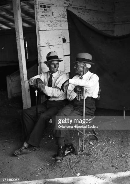 Photograph taken at the 1938 Oklahoma State Fair shows two stockmen taking a break near a Kreso Dip sign Oklahoma City Oklahoma 1938