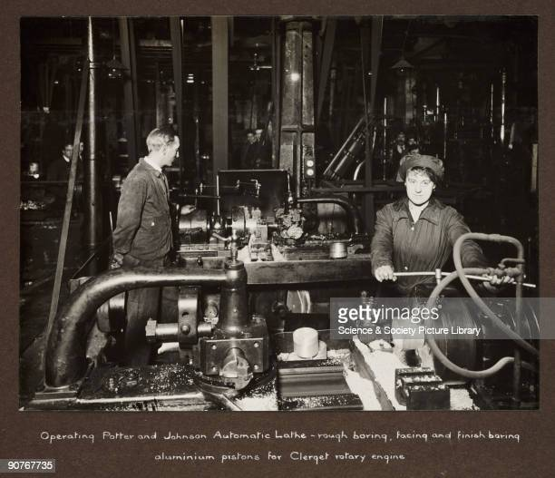 A photograph taken by an unknown photographer during 19151918 of a woman operating a machine lathe in a British factory A male supervisor stands...