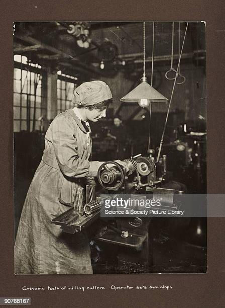 A photograph taken by an unknown photographer during 19151918 of a woman working in a British factory A woman stands over a machine at her...