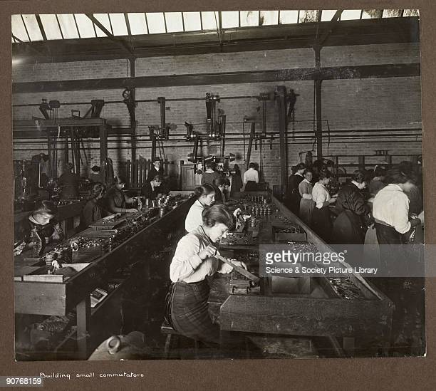 A photograph taken by an unknown photographer during 19151918 of a group of women working in a British factory The women work four to five a row at...