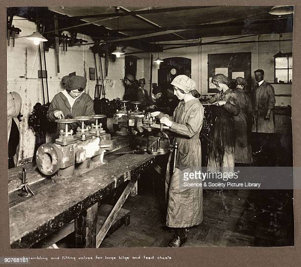 A photograph taken by an unknown photographer during 19151918 of a small team of women at work in a British factory Women work either side of a long...