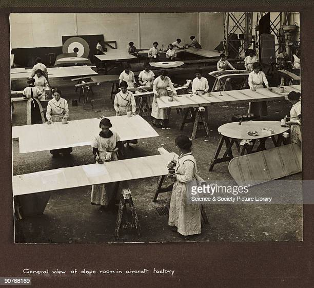 Photograph taken by an unknown photographer during 1915-1918 of a large team of women working in a British aircraft factory. The aeroplane frame is...