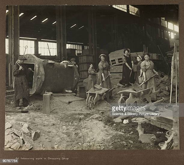 A photograph taken by an unknown photographer during 19151918 of people at work in a British labouring yard Men and women labour with spades hammers...