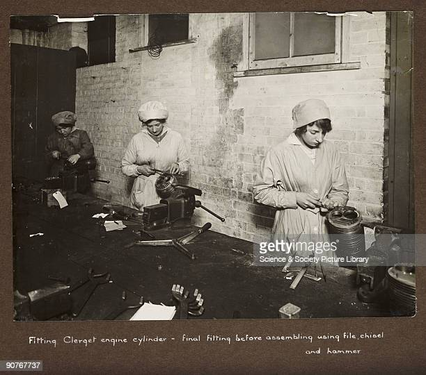 A photograph taken by an unknown photographer during 19151918 of three women working in a British factory Women stationed at a long workbench engage...