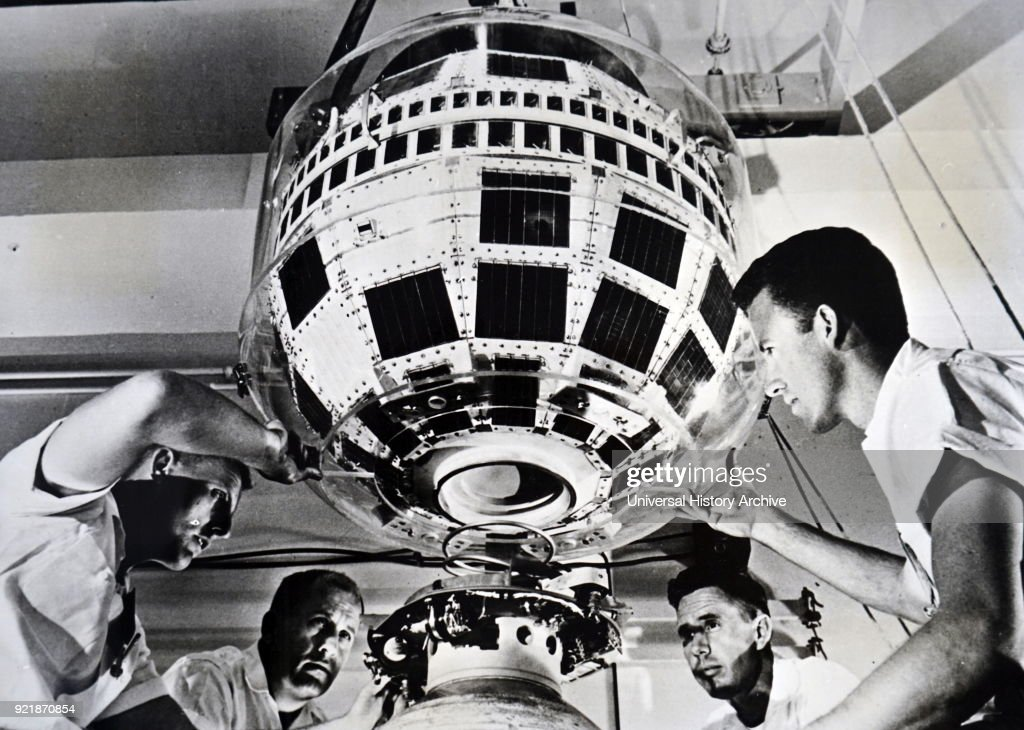 Photograph taken during the production of the Thor-Delta rocket. Technicians mate the Telstar communications satellite to the third stage of the rocket. Dated 20th century.