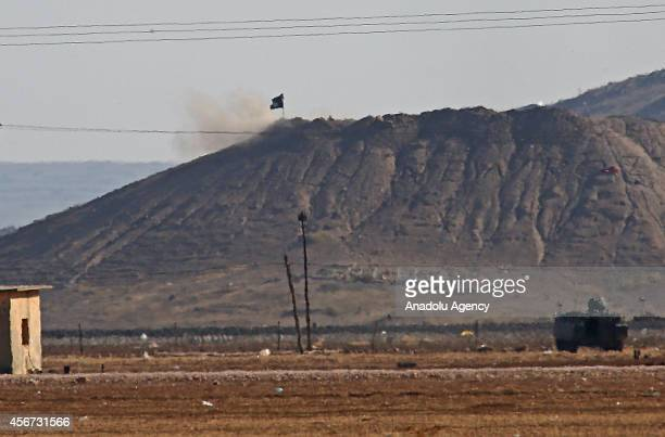 Photograph taken from Suruc district of Sanliurfa shows an Islamic State of Iraq and the Levant flag on the hill in the Syrian town of Ayn al-Arab on...