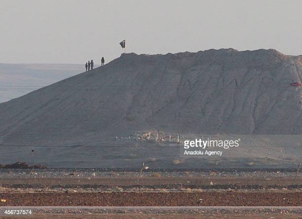A photograph taken from Suruc district of Sanliurfa shows an Islamic State of Iraq and the Levant flag on the hill in the Syrian town of Ayn alArab...