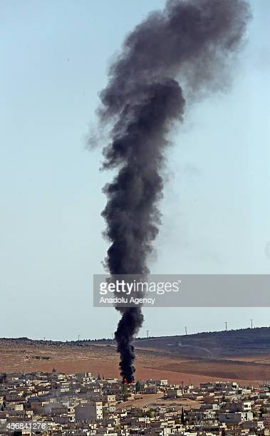 A photograph taken from Suruc district of Sanliurfa Turkey shows black smoke rises from Syria's Ayn alArab city following the shelling during the...