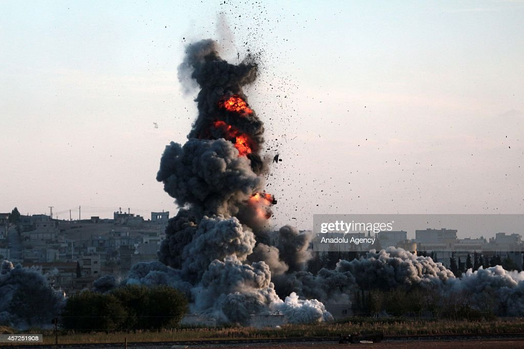 A photograph taken from Suruc district of Sanliurfa, Turkey, shows smoke rising from the Syrian border town of Kobani (Ayn al-Arab) following the US-led coalition airstrikes against the Islamic State of Iraq and the Levant (ISIL) on October 15, 2014.