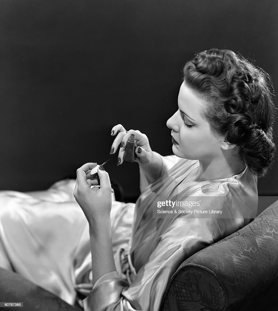 Woman sitting in a chair painting her nails, c 1940s. : News Photo