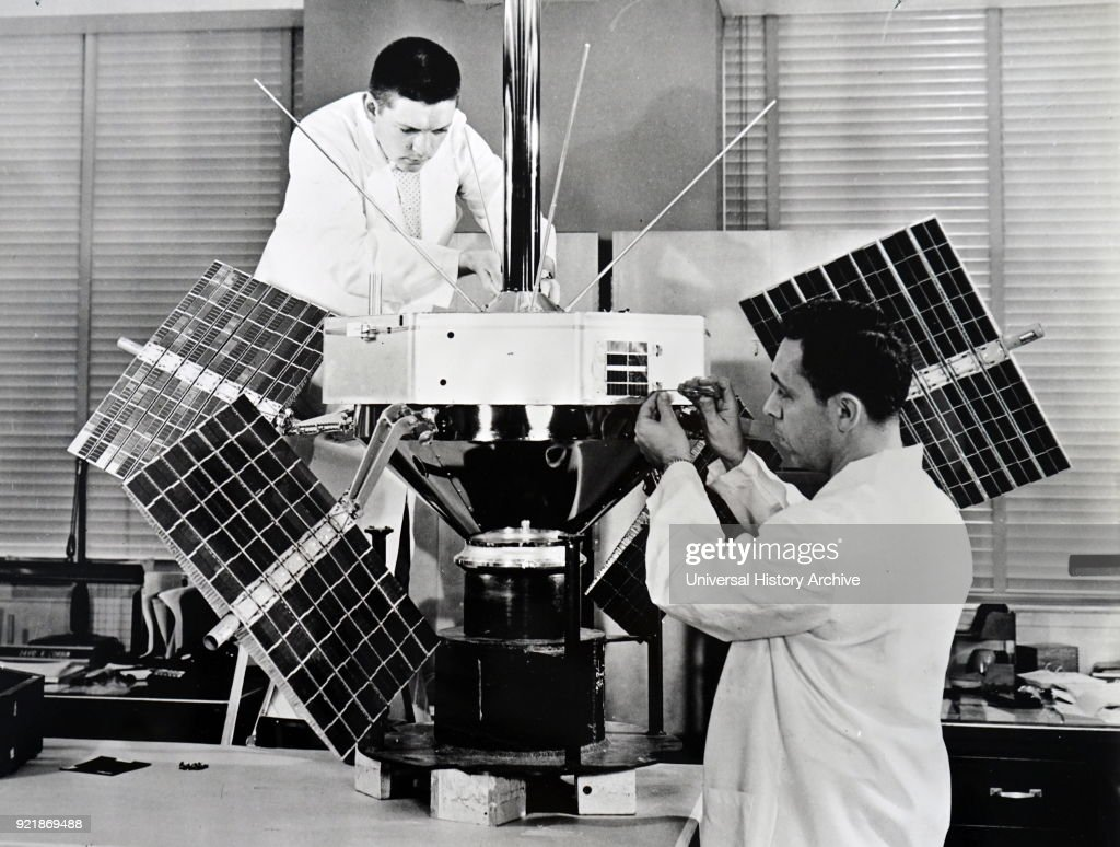 Photograph taken of scientists working on the S-3 spacecraft's final assembly fixture. (Left) Donald Bowers adjusts the antenna, whilst Lewis Paul works on the solar cell damage experiment (right). Dated 20th century.
