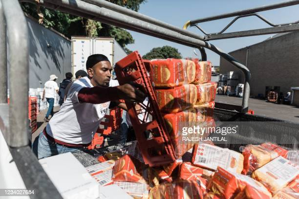 Photograph taken on July 17, 2021 shows a volunteer from Muslims For Humanity offloads a crate of bread at the NMJ Islamic Centre to distribute to...
