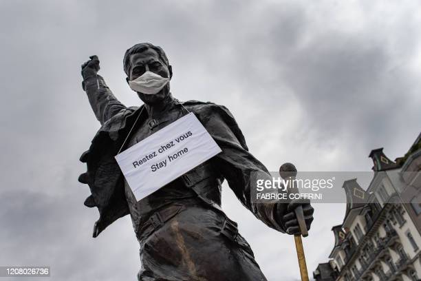 A photograph taken on March 23 2020 in Montreux shows the statue of Queen's late singer Freddie Mercury wearing a protective facemask and adorned...