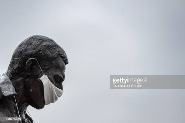 A photograph taken on March 23 2020 in Montreux shows the statue of Queen's late singer Freddie Mercury wearing a protective facemask on the shore of...