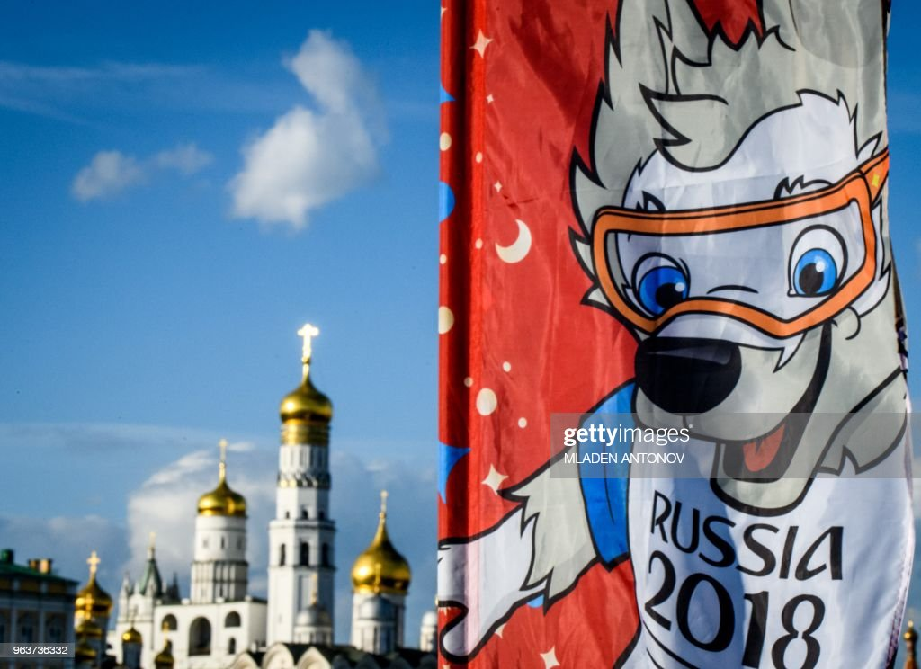 A photograph taken on May 30, 2018 shows the FIFA World Cup 2018 flag featuring the tournament's mascot Zabivaka in front of the Kremlin in Moscow. - The FIFA World Cup 2018 tournament kicks off on June 14, 2018.