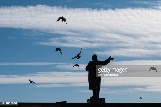 TOPSHOT A photograph taken on September 19 2017 shows some birds flying around a monument to the founder of the Soviet Union Vladimir Lenin in Nizhny...