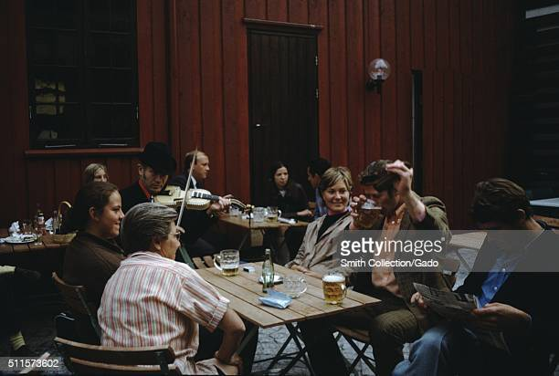 A photograph that features a family around a table at a pub the father is entertaining the women of the family by drinking his beer vigorously the...