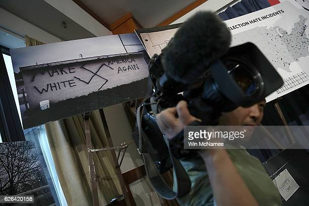 A photograph with a swastika and chart showing incidents of post election hate crimes are shown during a press conference November 29 2016 in...