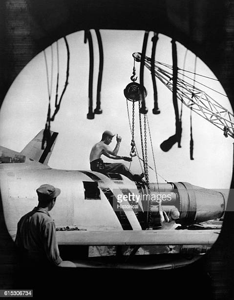 Photographed through the tailpipe of an F86 Sabre in September of 1951 an aircraft maintenance crew of the US Air Force 4th FighterInterceptor Wing...