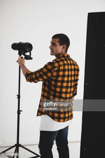 photographer adjusting lighting equipment in studio - photographe professionnel photos et images de collection
