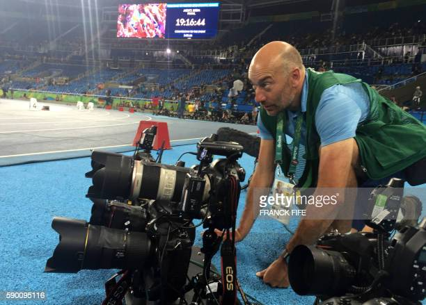 AFP Photographer Adrian Dennis prepares his remote controlled cameras before the final of the 100m Men's final at Rio 2016 Olympic games on August 14...
