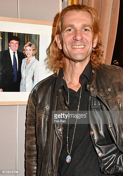 Photographer Ale de Basseville poses with a portrait of Donald Trump during the Massimo Gargia's Photos of Celebrities Exhibition at Mairie du 8eme...