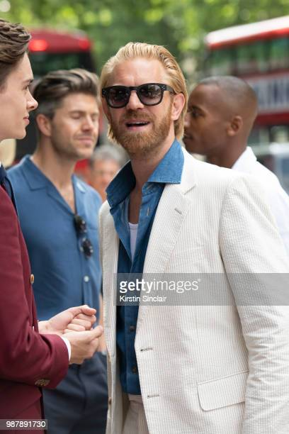 Photographer Alistair Guy wears an English Cut suit Celine sunglasses and Tommy Hilfiger shirt London Fashion Week Men's on June 10 2018 in London...