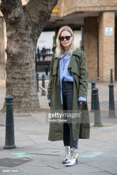 Photographer and blogger Jessie Bush wears a topshop Trench coat shirt and boots Levi's jeans Celine sunglasses on day 3 of London Womens Fashion...