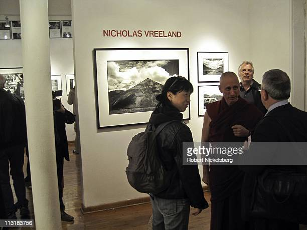 Photographer and Buddhist monk Nicholas Vreeland speaks, center right, with people attending the opening of his show of photographs taken in Tibet on...