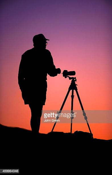 A photographer and camera tripod in silhouette at dawn