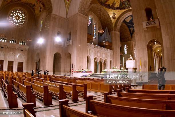 A photographer and cameramen record images of Reverend Wilton D Gregory Archbishop of Washington as he celebrates an Easter Sunday mass in front of...