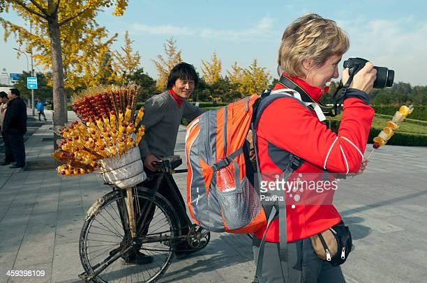 photographer and crystallized fruit seller beijing - pavliha stock photos and pictures
