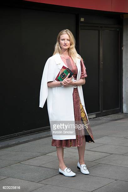 Photographer and Model Candice Lake wears Dorateymur shoes Christopher Esper jacket Burberry dress and bag day 4 of London Womens Fashion Week...