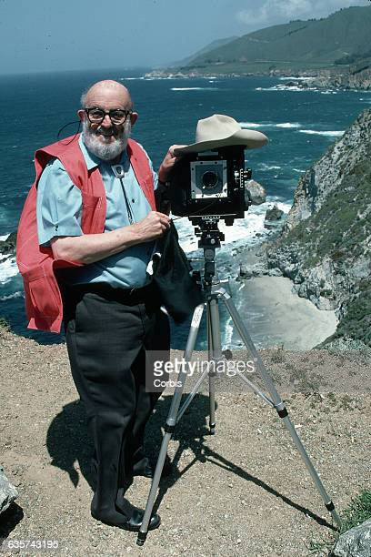 Photographer Ansel Adams stands on a bluff above the Pacific Ocean He uses his hat to shade his camera as he takes a picture | Location Near Highway...