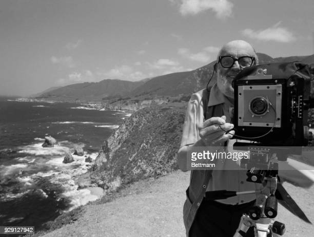Photographer Ansel Adams stands on a bluff above the Pacific Ocean He adjusts the settings on his camera