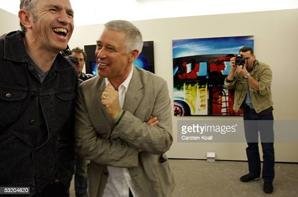 Photographer Anton Corbijn and Adam Clayton attend Corbijn's exhibition with pictures of rock band U2 July 6 2005 in Berlin Germany The exhibition...